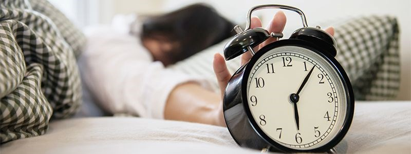 A sleeping person reaches for an alarm clock at 6:07 a.m.